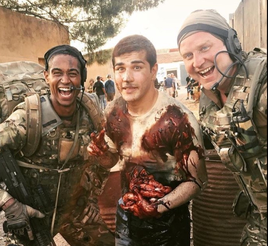 actors dressed as soldiers, one bloodied